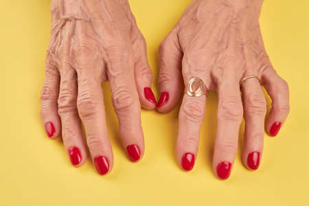 salon background: Elderly woman hands with red manicure. Senior woman hands with red nails on yellow background. Old woman hands with perfect red manicure.