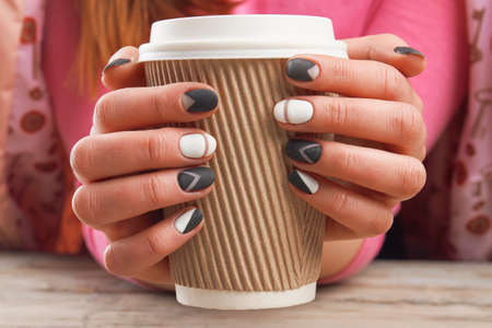 salon background: Manicured hands holding cardboard cup. Female hands with perfect manicure holding disposable cup of coffee. Time for beauty and relax. Stock Photo