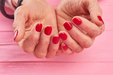 salon background: Female hands with perfect red nails. Hands of senior woman with beautiful red manicure on pink wooden background close up. Perfect manicure concept. Stock Photo