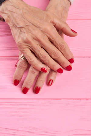 salon background: Female manicured hands on wooden background. Senior woman hands with beautiful red manicure on pink wooden background. Nail salon and spa. Stock Photo