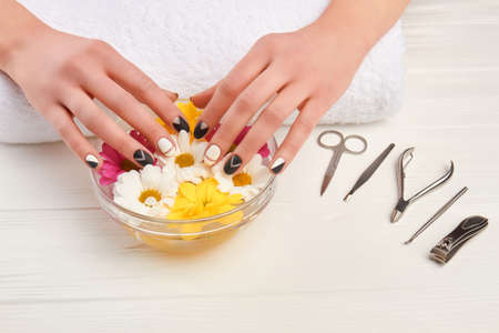 Female manicured hands in aroma bath. Woman receiving manicure procedure in spa salon. Nails and hands care.