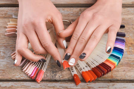 salon background: Female hands choose peach cnail color. Woman hands holding color nail polish on old wooden background.