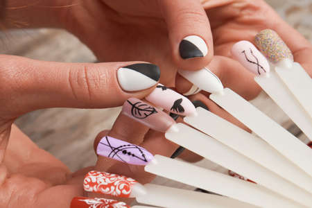 Manicured hands holding color nail samples. Manicure nail color design samples in female hands. Design templates for beauty salon.
