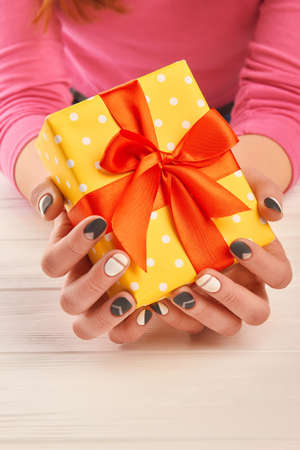 salon background: Hands with stylish manicure holding gift box. Female manicured hands holding yellow dotted box with gift on white wooden background. Holidays and celebrations concept. Stock Photo