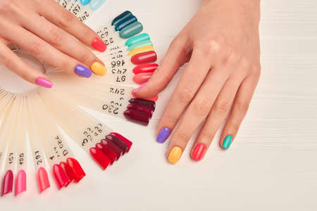 Well-groomed hands and nail color samples. Female hands with pastel manicure and nail color palette. Manicure nail polish color samples. Stock Photo