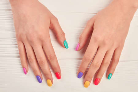 polished: Female hands with multicolored varnish on nails. Girl hands with nails polished with different colors. Summer fashion manicure.
