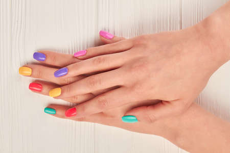 polished: Female hands with bright summer manicure. Woman hands with pastel polish on nails. female hands with summer colorful manicure. Stock Photo