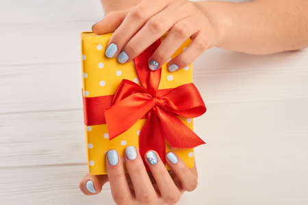 Yellow gift box in female hands. Beautiful woman manicured hands with gift box. Box with gift and winter fashion manicure. Stock Photo
