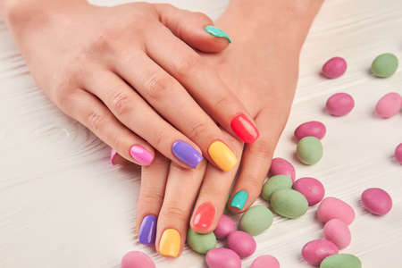polished: Multicolored manicure and candies close up. Female hands with stylish colorful nails and multicolored candies on white wooden background close up.