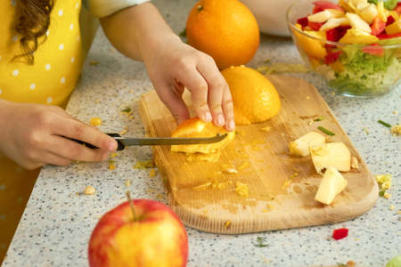 Hands of child cutting orange. Fruit on cooking board.