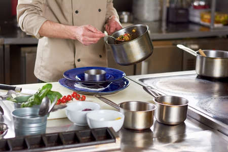 stewing: Chef put out with spoon stewing vegetables. Cropped image of male chef going putting garnishing into stainless bowl. Food preparation at professional kitchen.