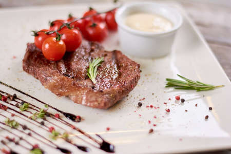 europeans: Steak ribeye with sauce from madagascar pepper.Tasty dish of restaurant with european cuisine. Appetizing food on white porcelain plate.