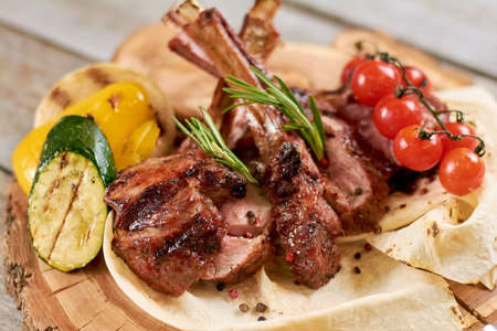 Roasted calf ribs with grilled vegetables. Juicy calf ribs with cherry tomatoes, zucchini, pepper and onion close up. Stock Photo