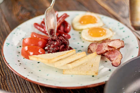 Full english breakfast on plate. Chef putting beans on plate with english breakfast. English breakfast in restaurant.