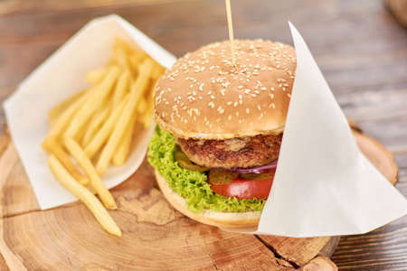 Burger with fried potatoes on wood. Classic american food - burger. Appetizing burger with fresh vegetbles, meat and french fries. Stock Photo