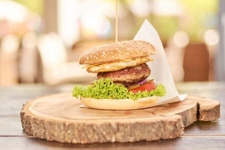 Appetizing cheeseburger on wood. Big humburger with cutlets, cheese, tomatoes, lettuce, onion, pickled cucumbers. Classic american food.
