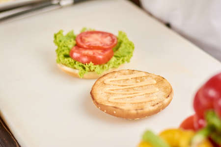 adding: Burger cooking at kitchen. Burger with lettuce and tomatoes on table. Burger preparing at cafe. Stock Photo