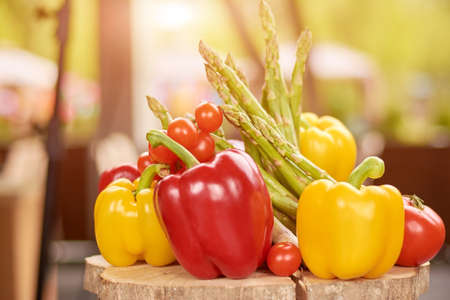 Close up of fresh peppers, asparagus, cherry tomatoes. Still life with fresh colorful vegetables on natural wood. Organic and fresh vegetables.