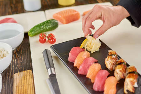 Chef adding ginger to sushi on plate. Cook serving sushi nigiri with ginger. Appetizing sushi in restaurant.