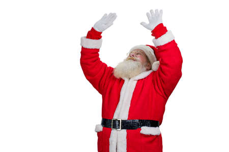 Santa Claus with raised hands, white background. Old Santa Claus with real beard raised hands and looking upwards on white background. Realistic Santa Claus making a magic.