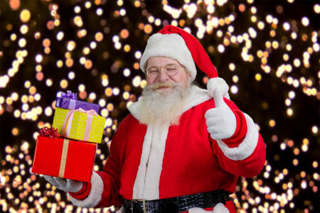 Santa with gifts showing thumb up. Santa Claus holding a pile of gifts boxes and giving thumb up on New Year lights background.