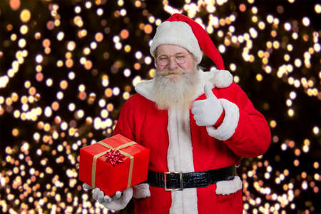 grandfather frost: Santa with present giving thumb up. Happy Santa Claus holding red gift box and giving thumb up on New Year lights background. Stock Photo