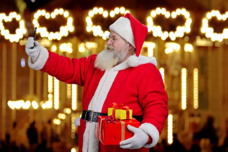 grandfather frost: Santa Claus taking a selfie on smartphone. Cheerful Santa Claus with gift boxes taking a picture with smartphone on festive lights background.