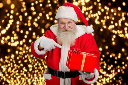 grandfather frost: Santa Claus holding beautiful red box. Authentic Santa Claus holding red gift box and pointing on it with his index finger, festive lights background. Happy santa Claus with present box.