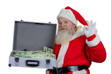 Santa Claus with open case full of money. Happy santa Claus holding ilver suitcase with dolars and showing ok gesture, isolated on white background.