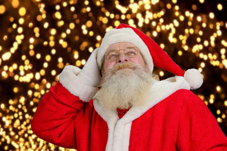 grandfather frost: Portrait of happy Santa Claus. Senior Santa Claus looking upwards on festive lights background close up. Cheerful Santa Claus enjoying festive New Year atmosphere.