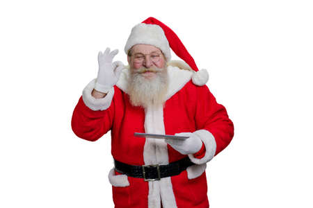 grandfather frost: Santa Claus with digital tablet. Senior Santa Claus is realizing kids wishes making a magic on white background. Santa Claus with touch screen tablet, studio shot. Stock Photo