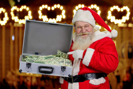 Santa Claus holding suitcase with money. Senior Santa Claus pointing with index finger on hundred dollars in briefcase, blurred background. Gift on Christmas holiday.