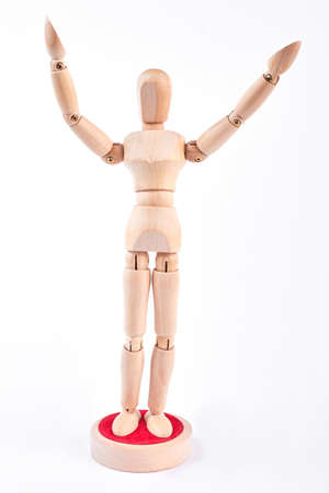 Wooden dummy standing with raised hands. Wooden mannequin raised hands over white background.