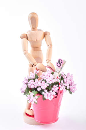 arm bouquet: Wooden dummy with bouquet of flowers. Wooden mannequin holding a gift for the eight of March. Gift on womans day.