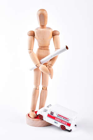Wooden dummy with white cigarette. Human wooden mannequin with tobacco cigarette, emergency ambulance on white background. Smoking and heart disease concept.