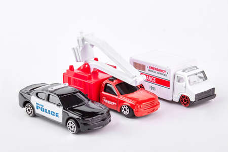 Close up of a toy ambulance with a fire engine and a police car on white background. Stock Photo