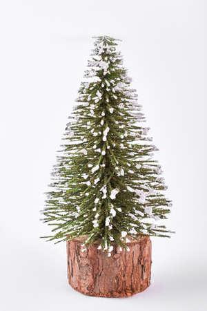 白い背景に分離された装飾的なクリスマスツリー。雪の降るおもちゃのクリスマスツリー。