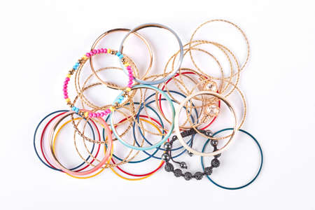 Stack of different wrist bands for women, white background. Female bangles on sale. Stock Photo