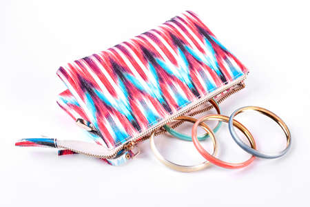 Fashion toiletry bag with modern bangles on white background close up. Woman fashion accessories. Stock Photo