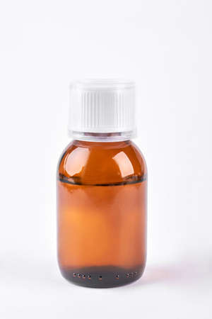 Cough syrup in glass amber bottle. Antipyretic syrup in brown bottle with plastic measuring cup on white background.