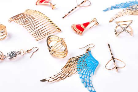 Woman fashionable golden accessories. Female golden rings, earrings, golden comb over white background. Ladies luxury accessories.
