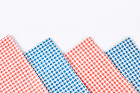 Plaid table napkins, white background. Collection of red and blue checkered tablecloth on white background close up. Row of vintage table napkins.