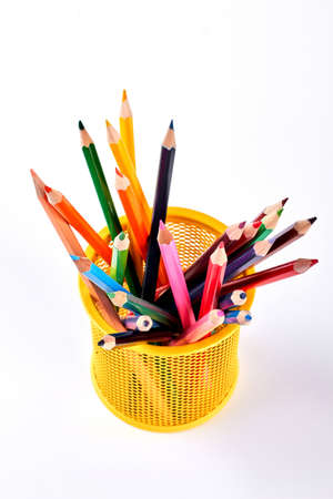 Multicolored pencils in metal pot. Yellow pen holder with colored pencils on white background, top view. Stock Photo