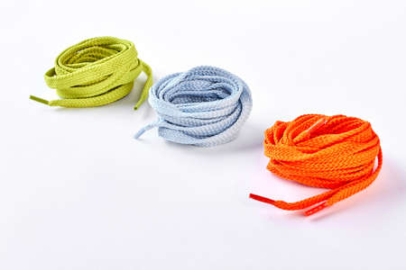 Rolls of colorful shoe laces, white background. Composition from colorful hoe stripes isolated on white bakground.