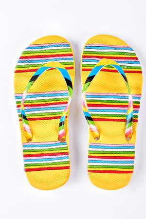 Summer fashion striped slippers. Yellow flip flops in colorful stripes isolated on white background. Fashion beach footwear. Foto de archivo