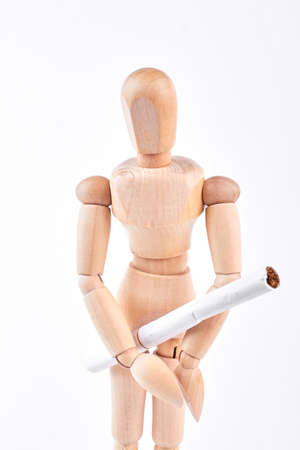 Wooden dummy with white cigarette. Human wooden mannequin holding cigarette with filter over white background. Stock Photo