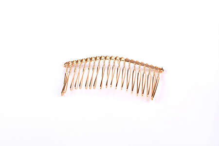 Metal hair comb on white background. Gold hair comb isolated on white background. Comb to create unique look. Stock Photo