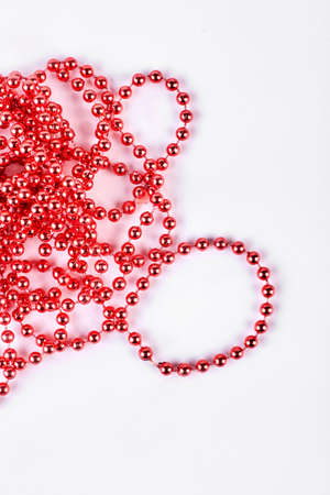 Red beads garland for decoration. Beautiful red necklace isolated on white background. Christmas decoration red beads isolated over white.
