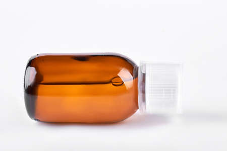 Antipyretic syrup in brown bottle. Cough syrup in glass brown bottle lying on white background. Mixture for cough treatment.