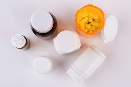 Antipyretic syrup, nasal spray, pills. Composition of medicine bottles and pills on white background, top view.